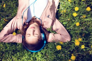 Teenage girl lying on back in the grass with hands behind head.She listens to music with eyes closed.